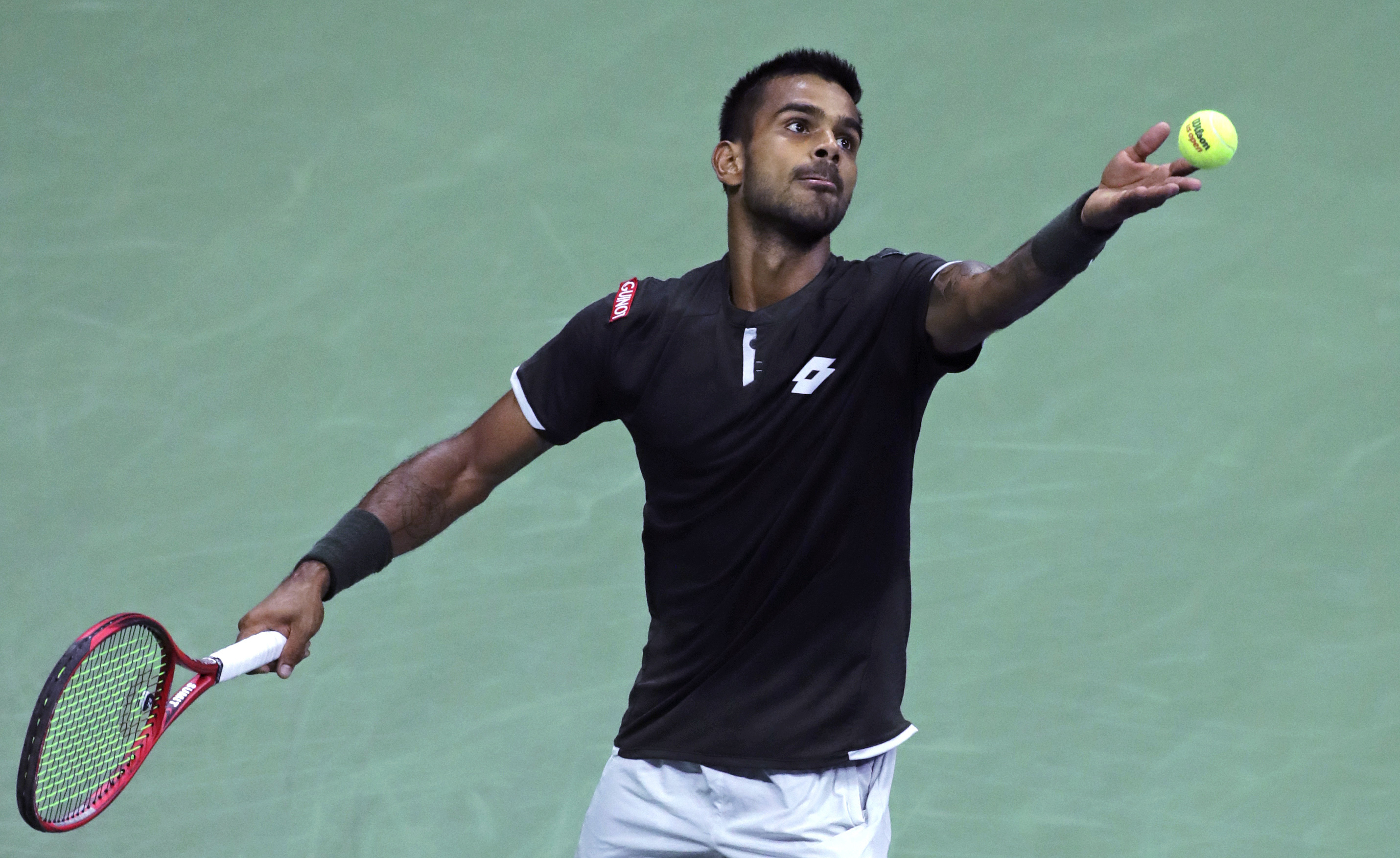 Sumit Nagal serves to Roger Federer in the first round of the US Open in New York.