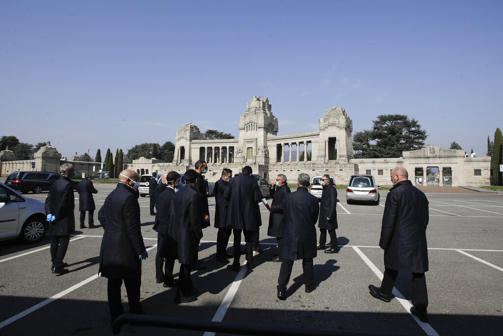 Pallbearers stand outside the Monumentale cemetery, in Bergamo, the heart of the hardest-hit province in Italy's hardest-hit region of Lombardy, Italy, on Tuesday