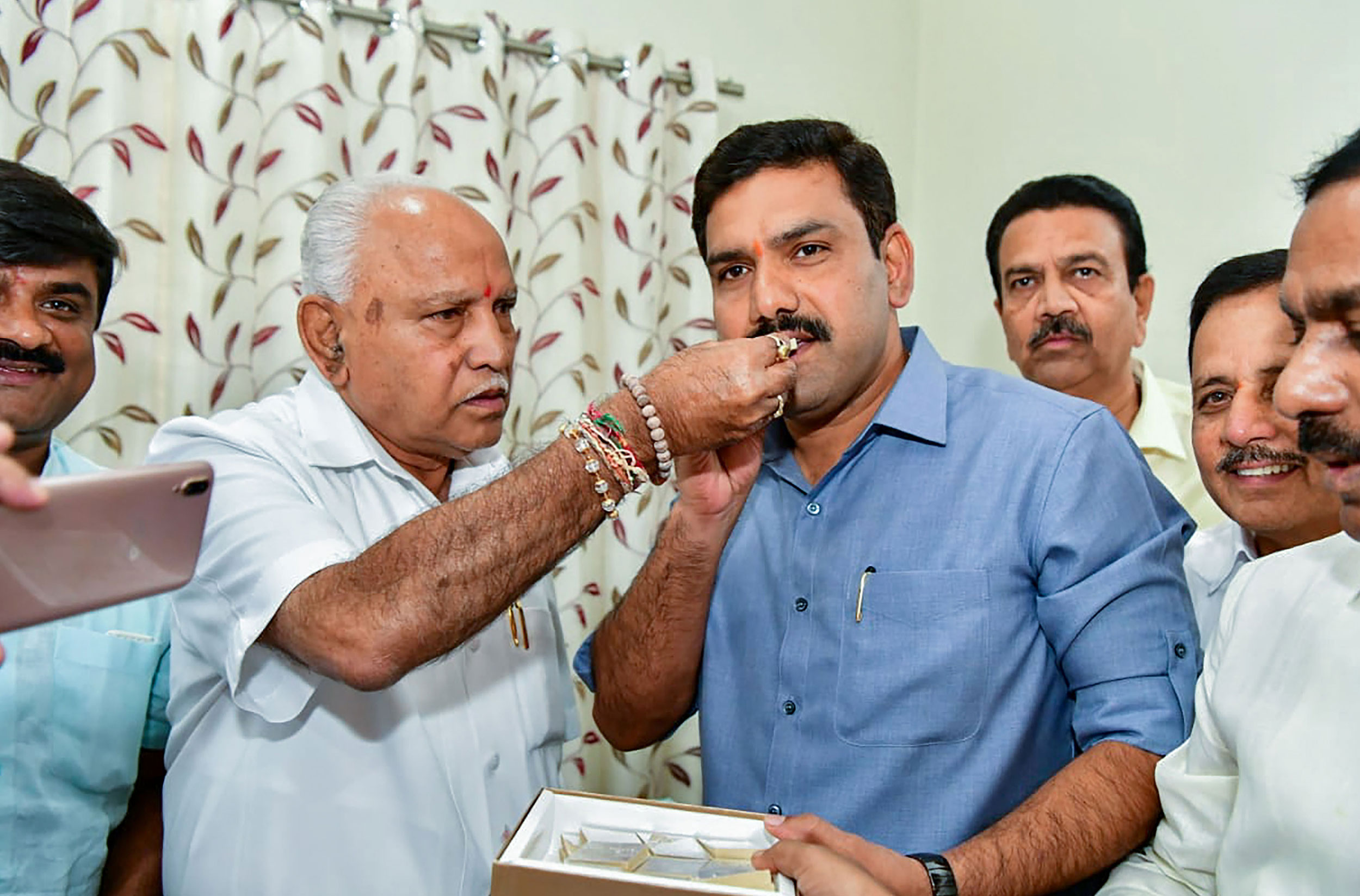 B.S. Yediyurappa offers sweets to BY Vijayendra after BJP won in 12 out of 15 Assembly constituencies in Karnataka, in Bangalore, on Monday.