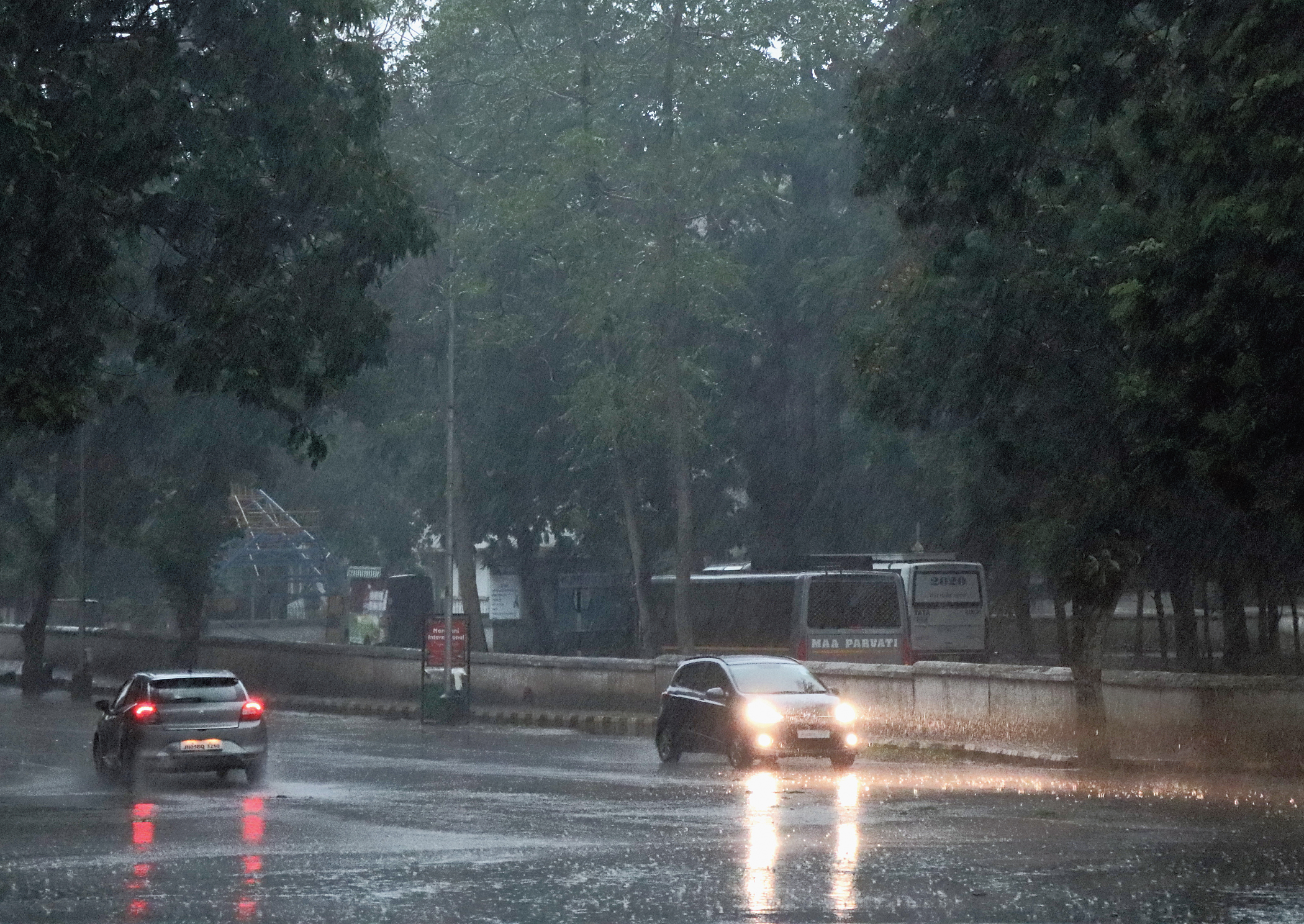 Vehicles move with headlights on during rain at Sakchi in Jamshedpur on Thursday afternoon.