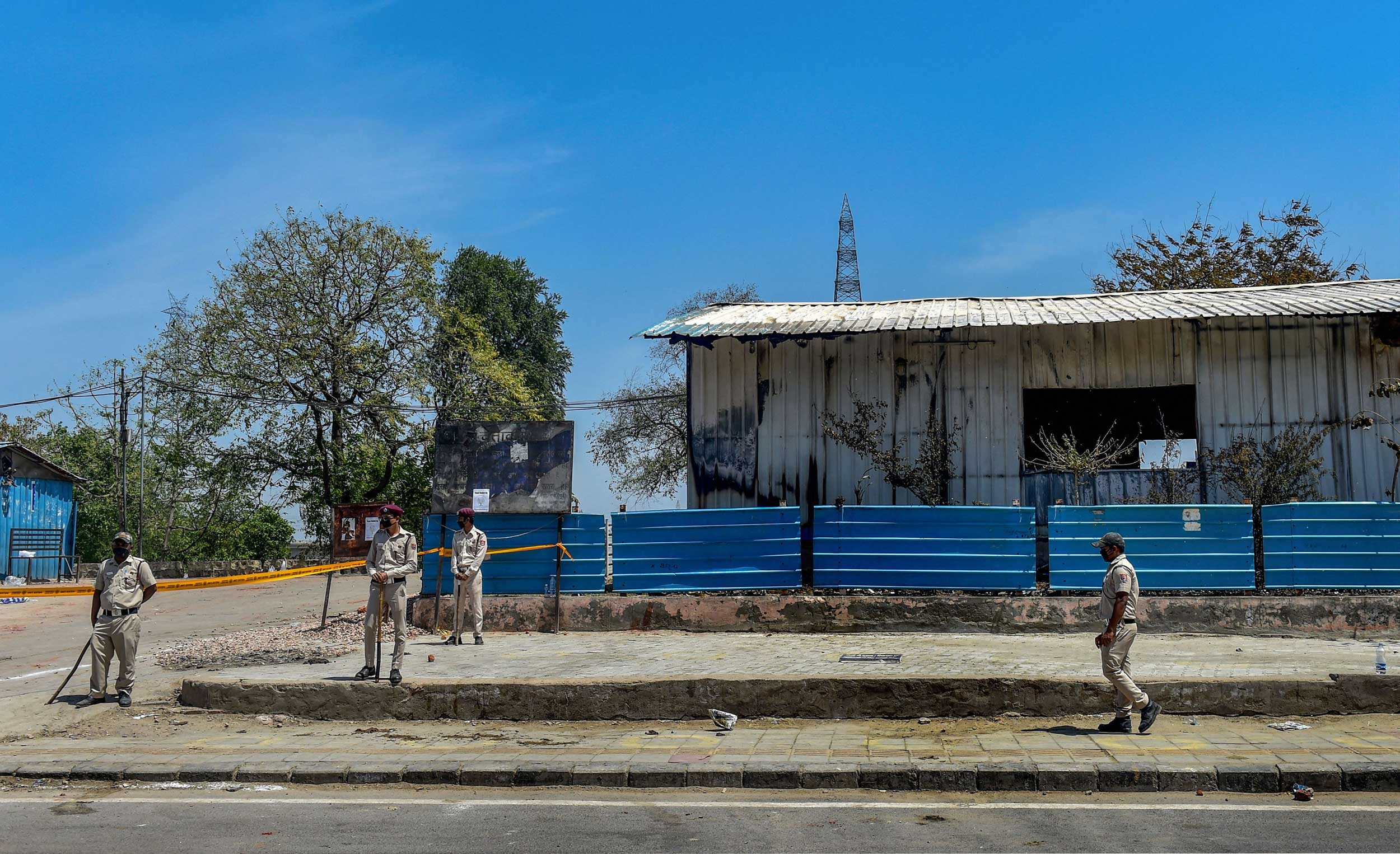 Civil defence volunteers stand guard outside a charred shelter home during the nationwide lockdown near Nigam Bodh Ghat in New Delhi on Sunday.