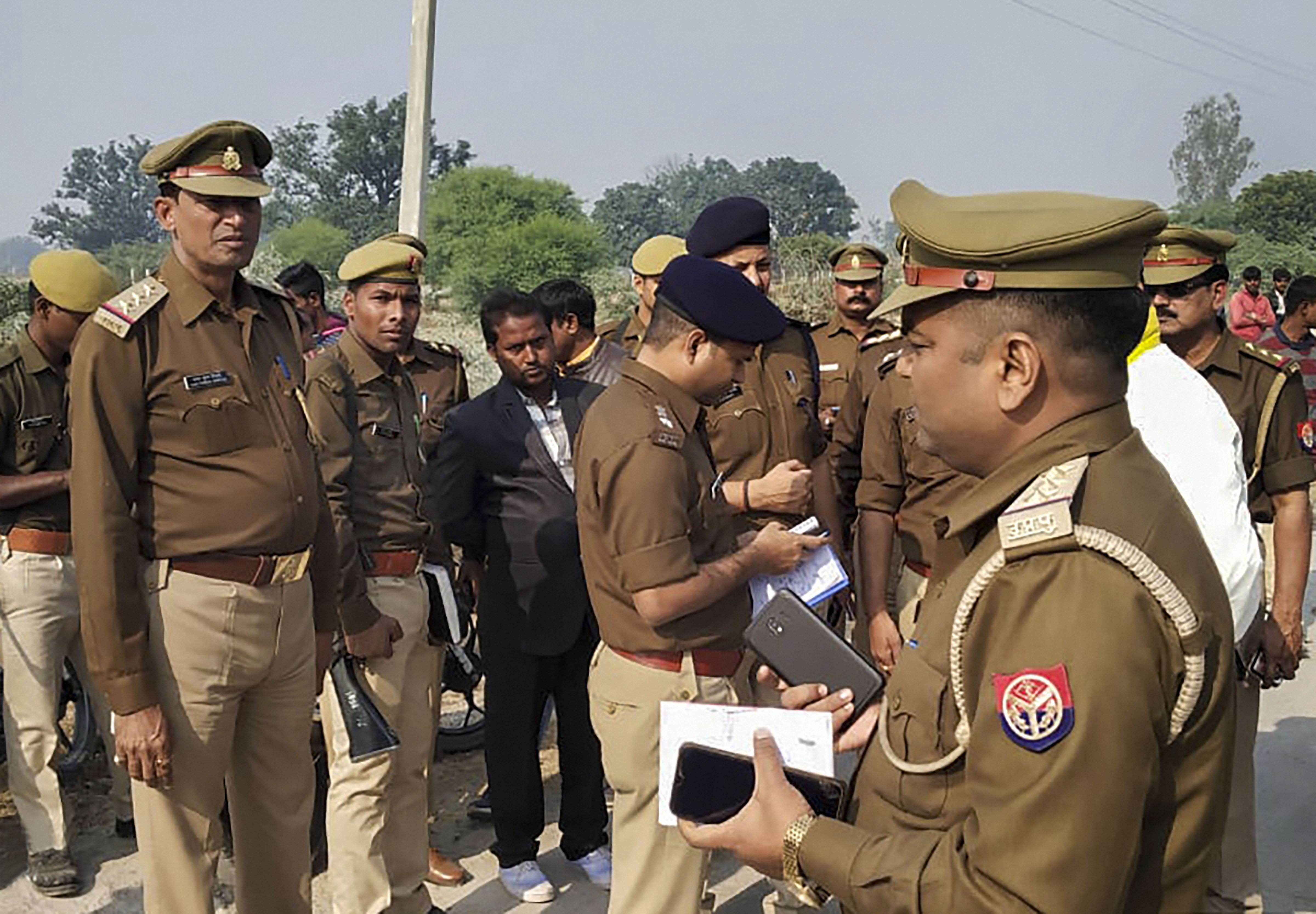 Police personnel investigate the site where the rape victim was allegedly set ablaze by five men at Sindupur village in Unnao district, Thursday, December 5, 2019.