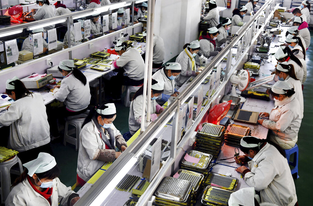 In this March 4, 2020, photo by Xinhua News Agency, workers wear mask labor in an electronic technology company in Mianxian County, Shaanxi province. China factories that make the world's smartphones, toys and other goods are trying to protect their employees from the outbreak.