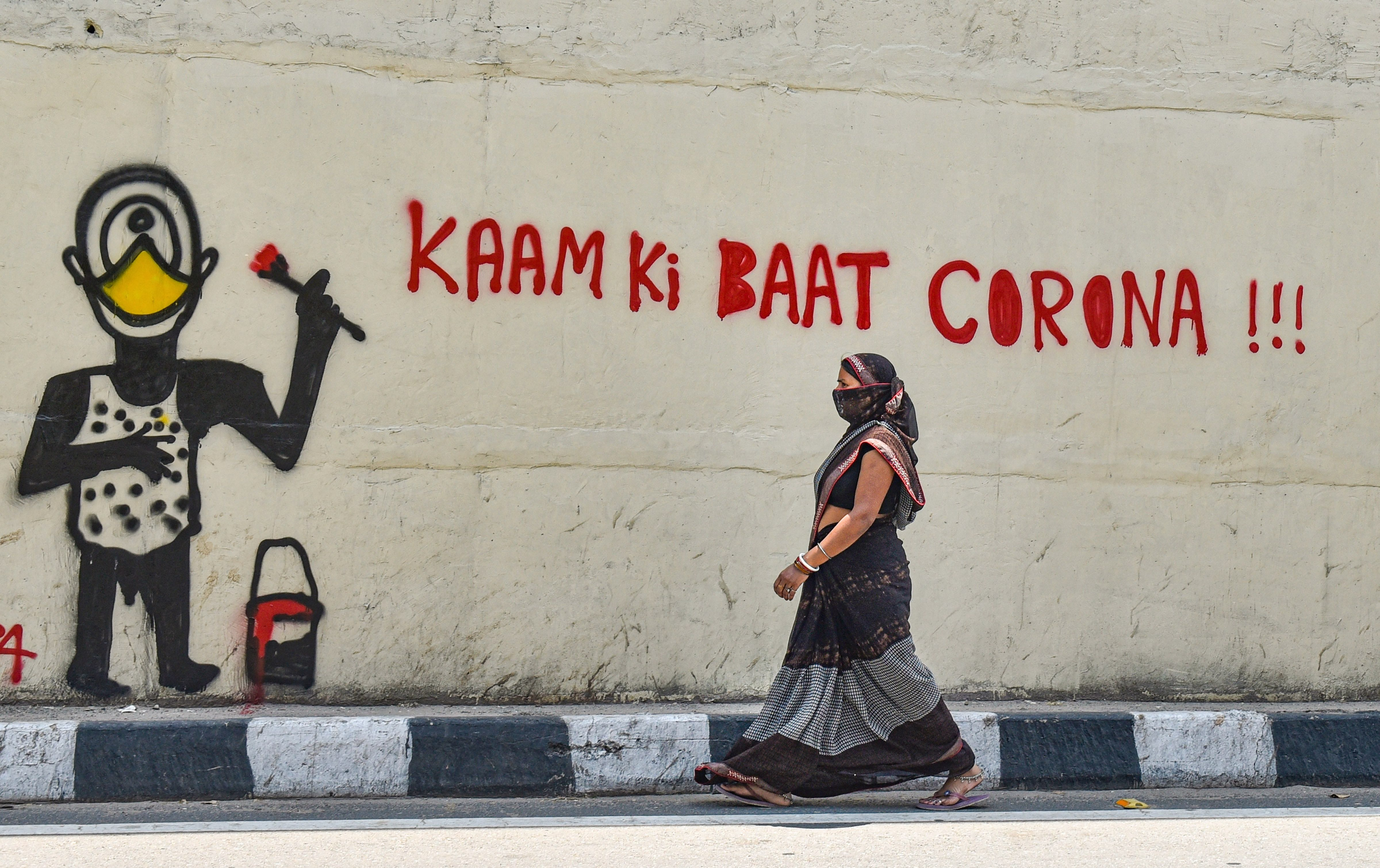 A woman walks past a wall with an awareness graffiti on coronavirus during the nationwide lockdown, in New Delhi, Tuesday, May 5, 2020.