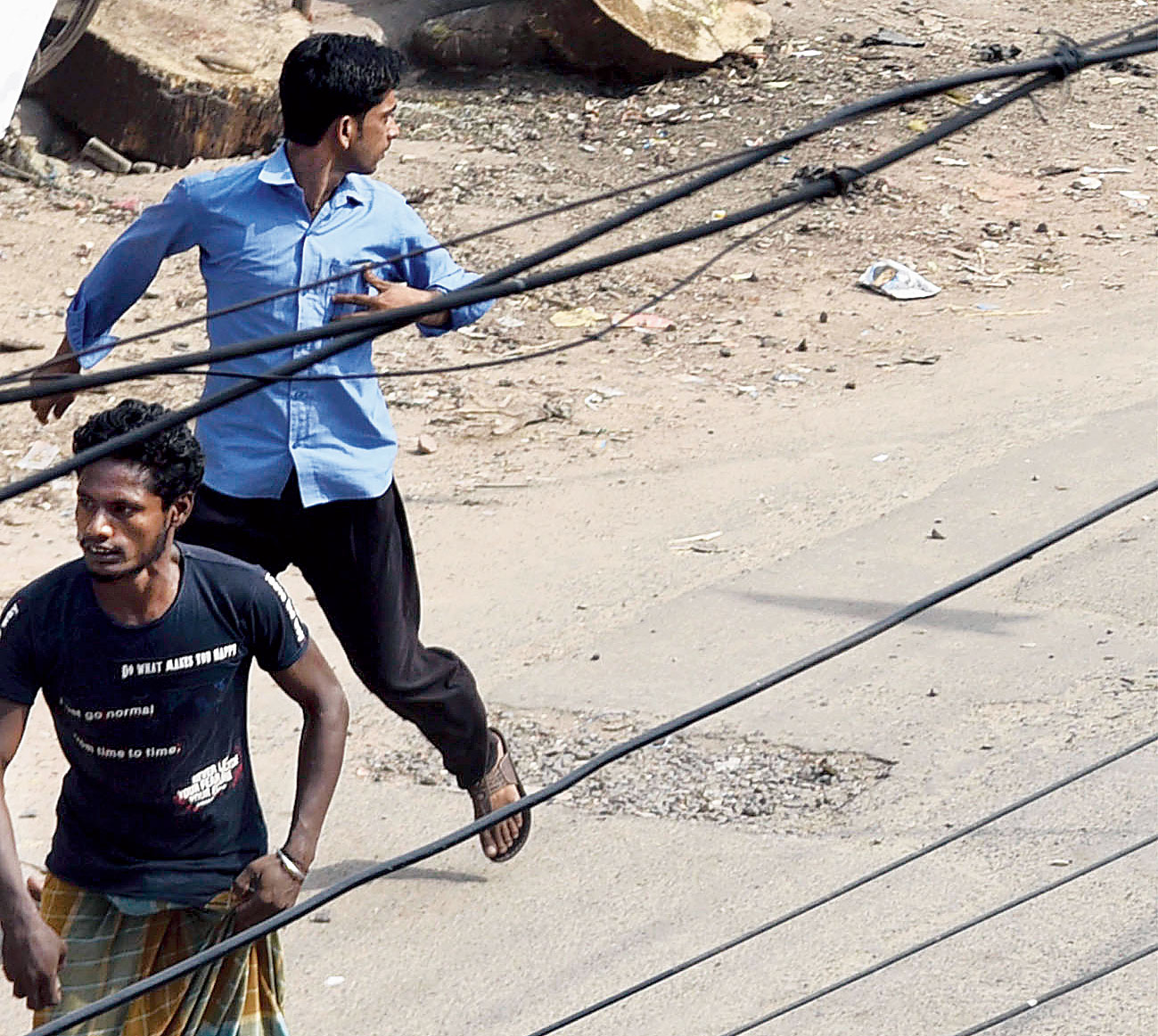 Two men run along a road in Bhatpara during the violence on Sunday afternoon.