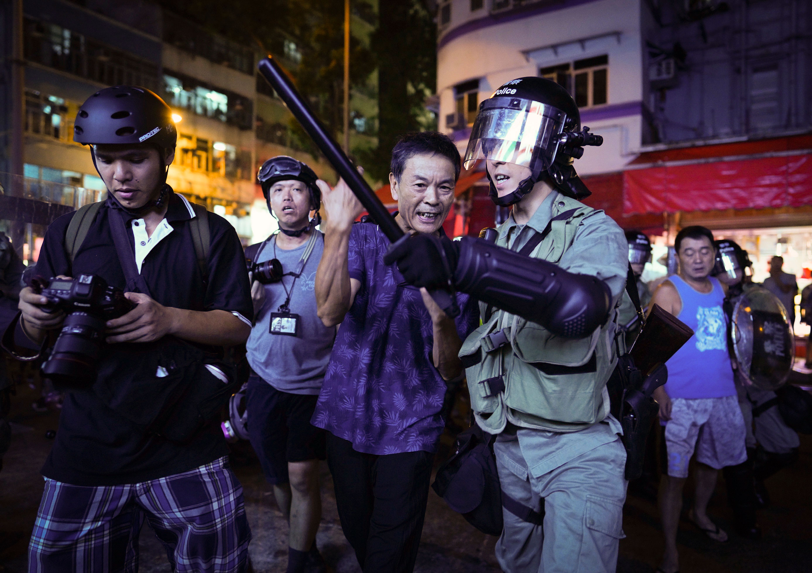 A Pro-China supporter is escorted by police after confronting journalists in north point, Hong Kong, on September 15, 2019.