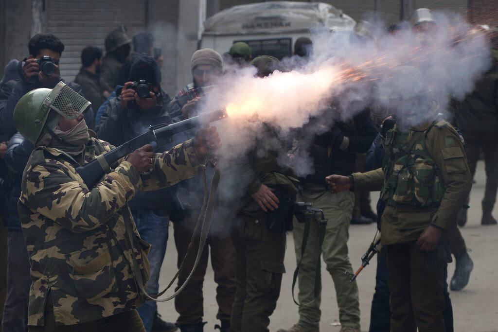 A paramilitary solider fires a tear gas shell towards Kashmiri protesters in Srinagar on Tuesday, February 26. Kashmiri protesters were protesting against raids on key separatist leaders by intelligence officers.