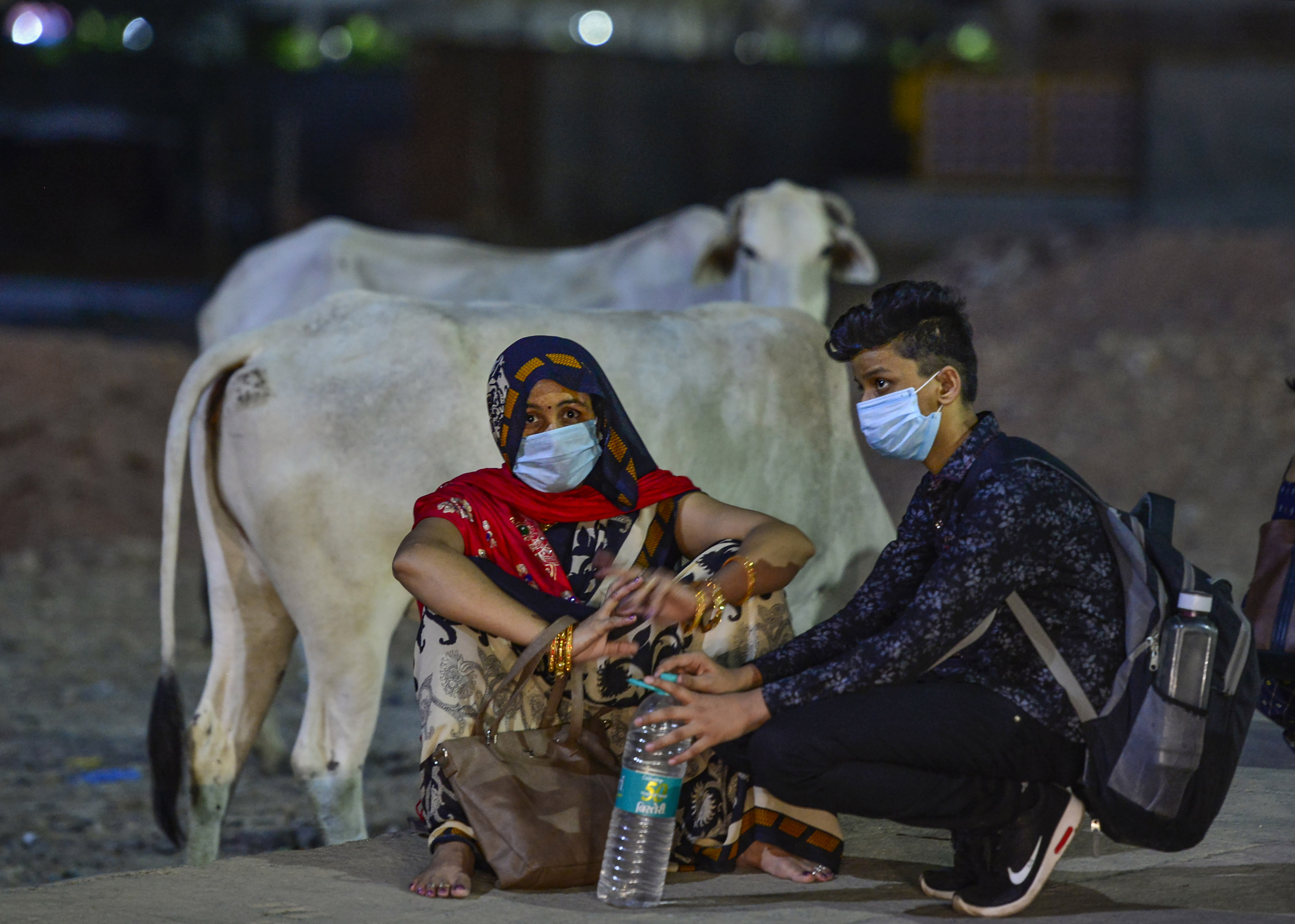 Migrants take rest near Ghazipur after being stopped by the police, during ongoing Covid-19 lockdown, in New Delhi, Monday, May 18, 2020