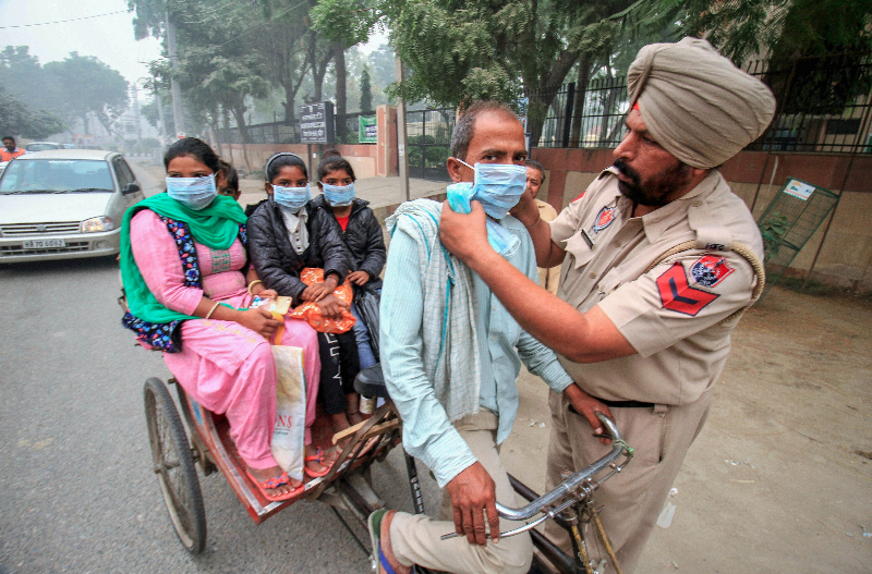 A police constable in Bathinda, Punjab, distributes masks to people in the street on Saturday, November 10, to protect them from the smog caused by the burning of crop stubble in fields in the region.