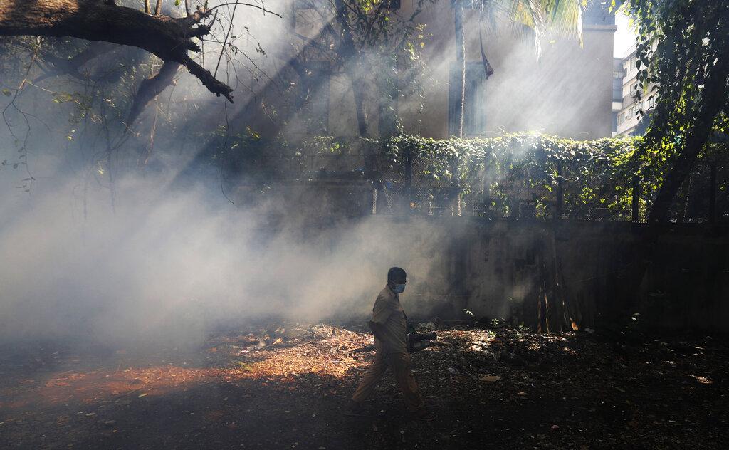 A Mumbai Municipal Corporation worker fumigates a neighborhood in Mumbai, Maharashtra state, on Wednesday, June 10, 2020.
