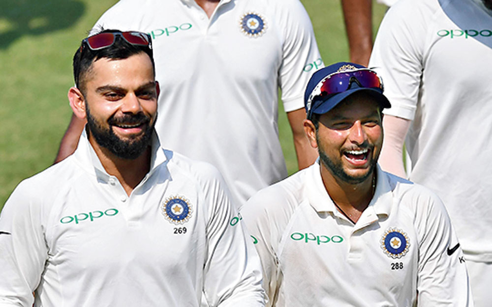 Indian captain Virat Kohli with teammate Kuldeep Yadav after winning the first Test cricket match between India and West Indies at the Saurashtra Cricket Association Stadium, Rajkot, on October 6, 2018