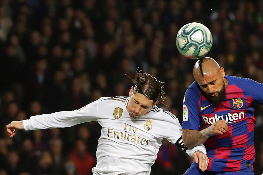 Real Madrid's Sergio Ramos, left, heads for the ball with Barcelona's Arturo Vidal during a Spanish La Liga match between Barcelona and Real Madrid at Camp Nou stadium in Barcelona, Spain, on Wednesday
