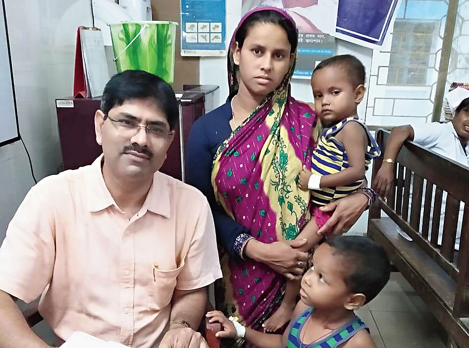 Doctor Mukherjee with the two children and their mother at the Raiganj Super Speciality Hospital