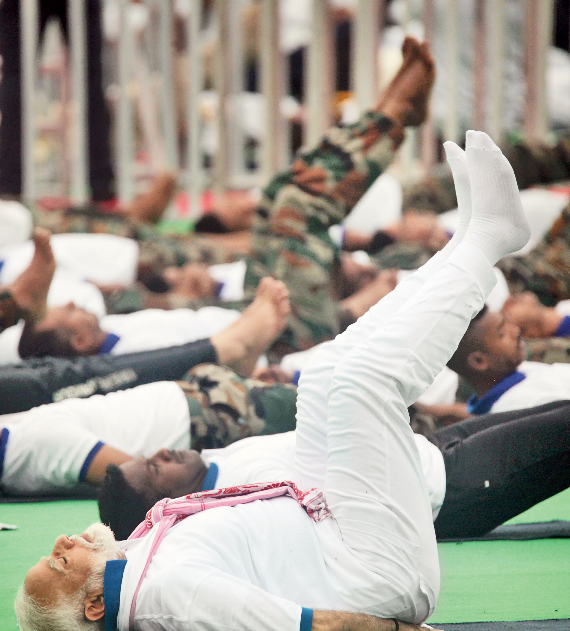 Prime Minister Narendra Modi performs the Uttana Padasana, which helps in relieving abdominal pain, indigestion, and depression, along with other yoga day participants at Prabhat Tara ground in Ranchi on Friday.