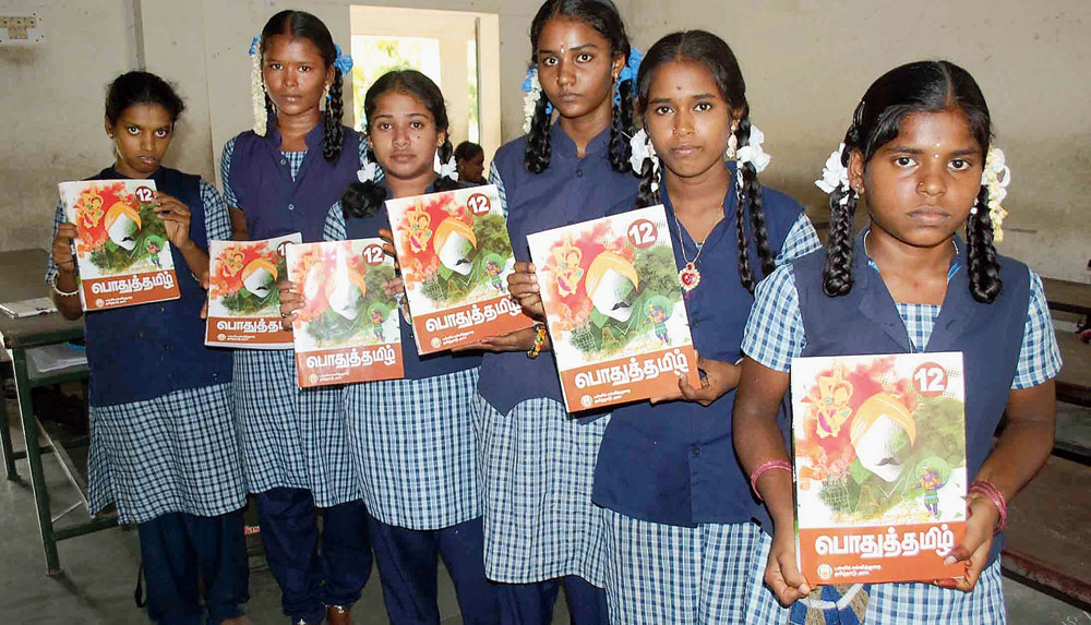 Students with Class XII textbooks that depict Subramania Bharati with a saffron turban.