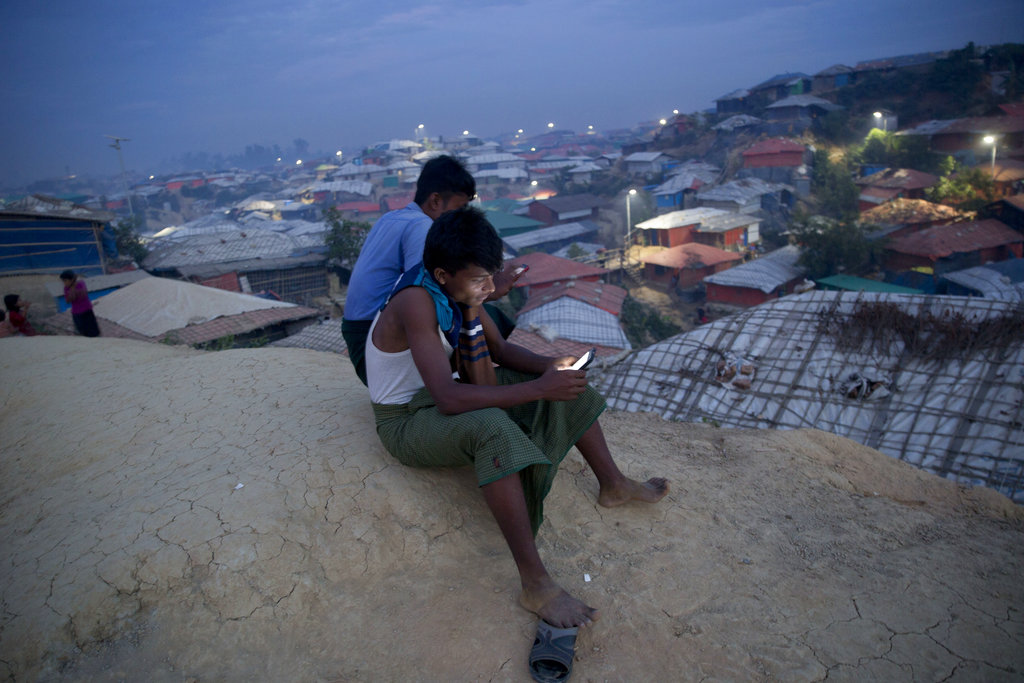 Rohingya Muslims sit on a hillock overlooking Balukhali refugee camp, in Bangladesh, on Wednesday.