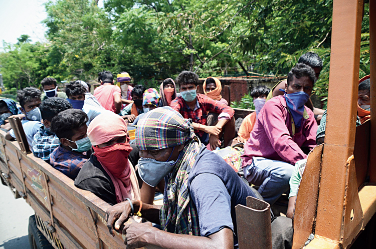 Labourers from Garwha, who were returning from Cuttack, on a truck at Hinoo Chowk in Ranchi; people walking on railway tracks at Dibdih near Hatia station in Ranchi.