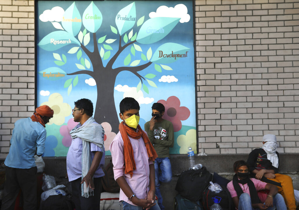 Migrant workers from other states wait in long queue to get his name registered so that they can board a train back to their villages during a nationwide lockdown to curb the spread of new coronavirus in New Delhi, on Thursday, May 21, 2020.