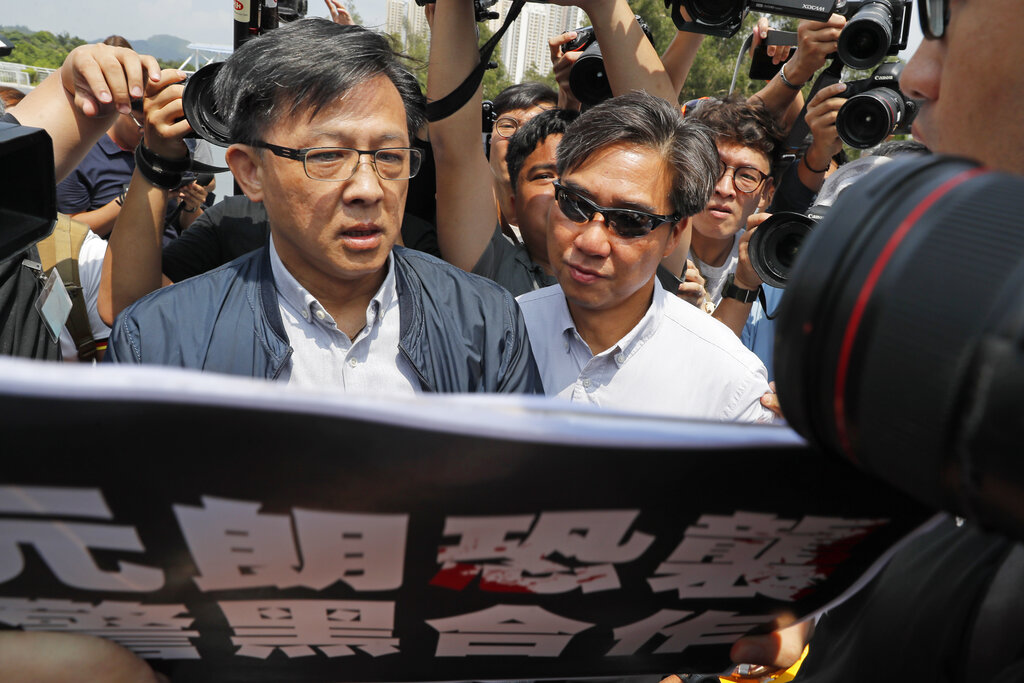 In this August 12, 2019, photo, pro-Beijing lawmaker Junius Ho (left) attends a demonstration of an anti-riot vehicle equipped with water cannon at the Police Tactical Unit Headquarters in Hong Kong.