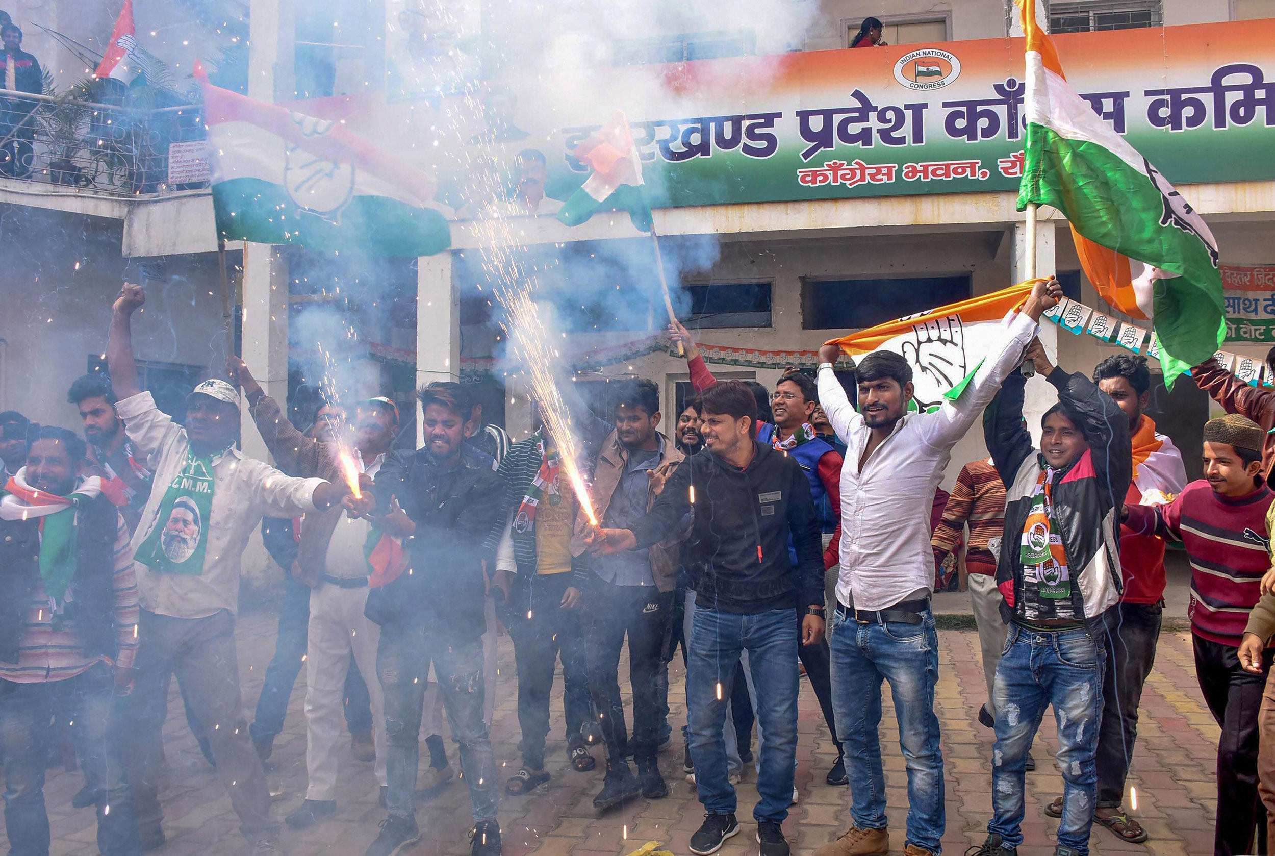 Jharkhand Mukti Morcha and Congress workers celebrate in Ranchi on Monday.