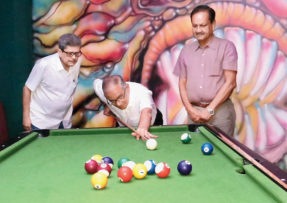 Pankaj Parekh takes aim to play a shot on the pool table at Levels The Club as publisher Tridib Chatterjee and former cricketer Sambaran Banerjee look on.