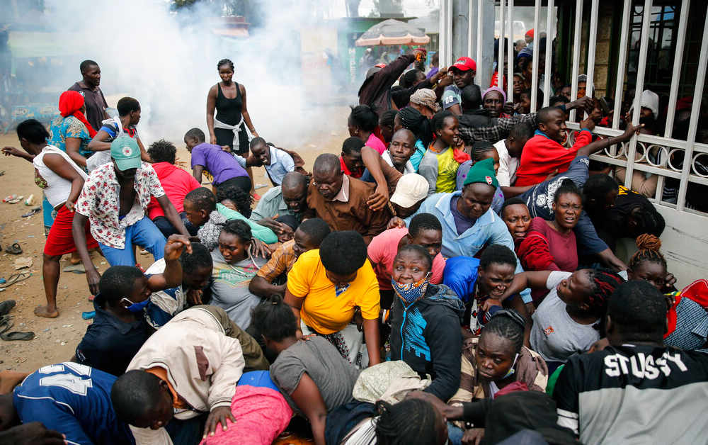 Residents desperate for a planned distribution of food for those suffering under Kenya's coronavirus-related movement restrictions push through a gate and create a stampede, causing police to fire tear gas and leaving several injured, at a district office in the Kibera slum.