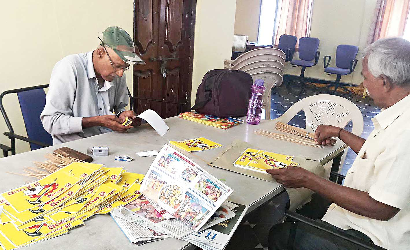 Prasad (in cap) and Subbarao make flags at a TDP office in Mangalagiri.