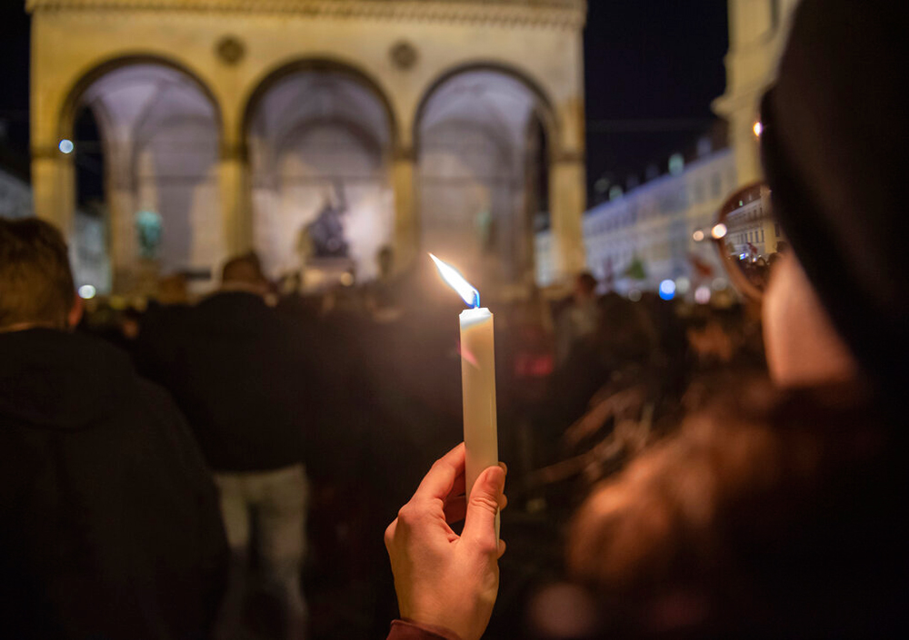 A woman holds a candle during a vigil in Munich city centre for the victims of the Hanau shooting