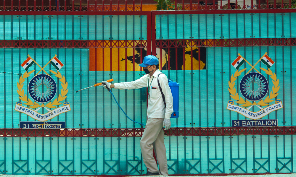 A municipal worker sprays disinfectants outside CRPF's 31 battalian building, during the ongoing COVID-19 lockdown, in East Delhi, Saturday, May 2, 2020. The number of Covid-19 personnel in the battalion has risen to 122.