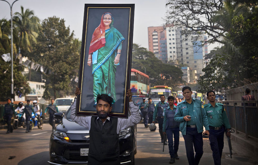 An Awami League supporter carries a photograph of Prime Minister Sheikh Hasina during an election rally in Dhaka.