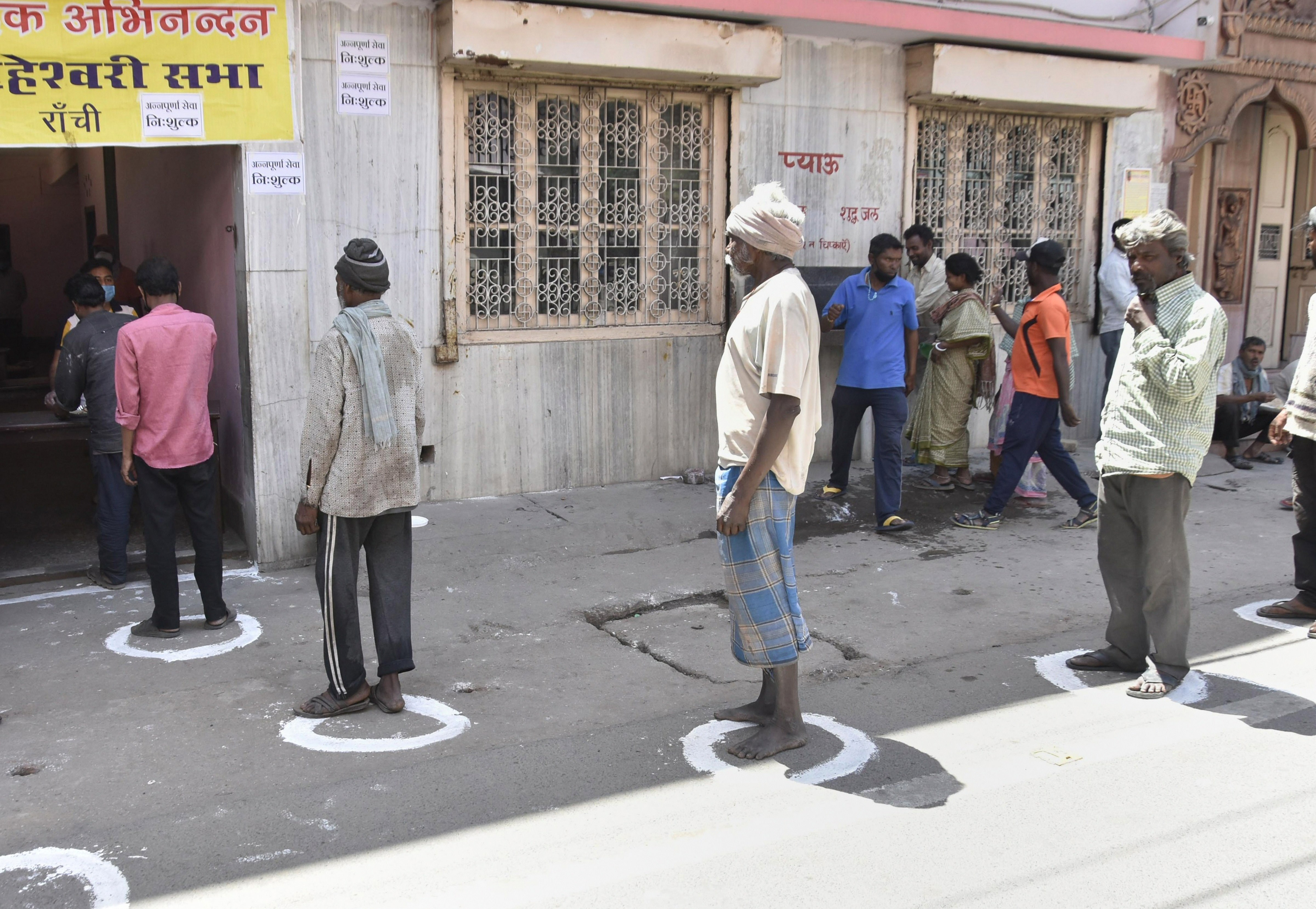 Labourers stand in a queue maintaining social distance as they collect free meals being distributed by a charitable society during total lockdown amid the coronavirus pandemic, in Ranchi, Thursday, March 26, 2020