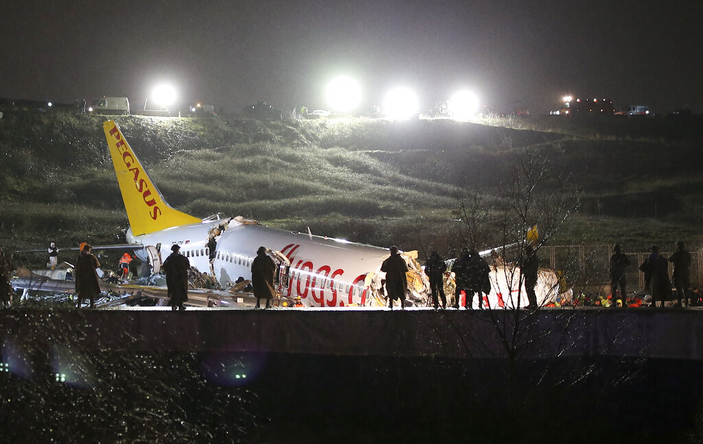 Rescue members and firefighters work after a plane skidded off the runway at Istanbul's Sabiha Gokcen Airport, in Istanbul, on Wednesday, February 5, 2020