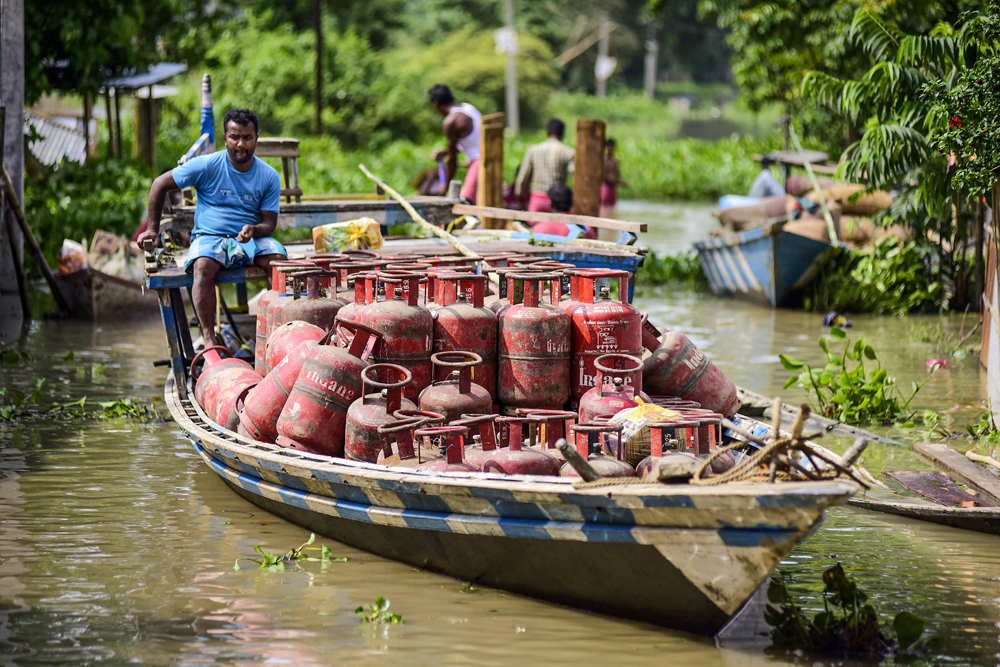 A flood-affected villager moves LPG cylinders loaded on a boat to a safer place, in Morigaon, Assam on Tuesday, July 16, 2019.