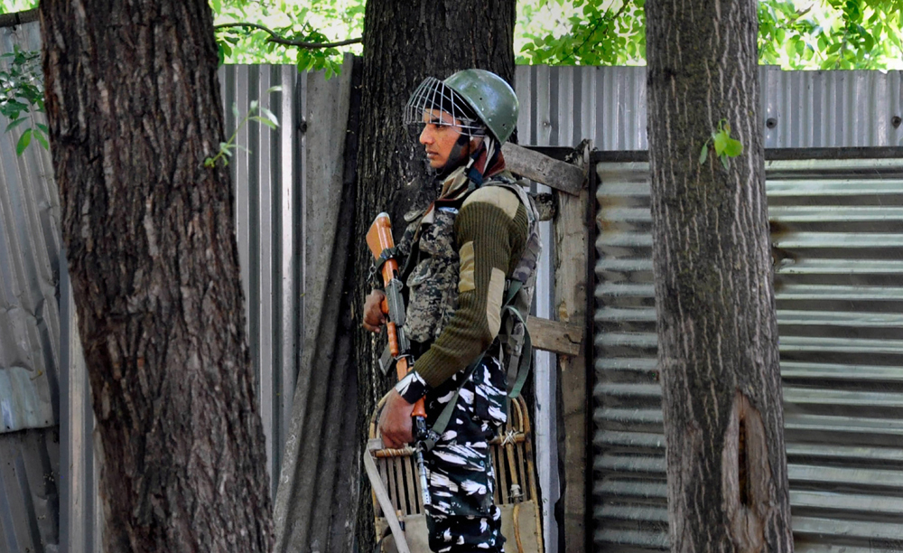 A security person stands guard near a polling station at Rahmoo, during the 5th phase of Lok Sabha elections in Pulwama on Monday, May 6, 2019.