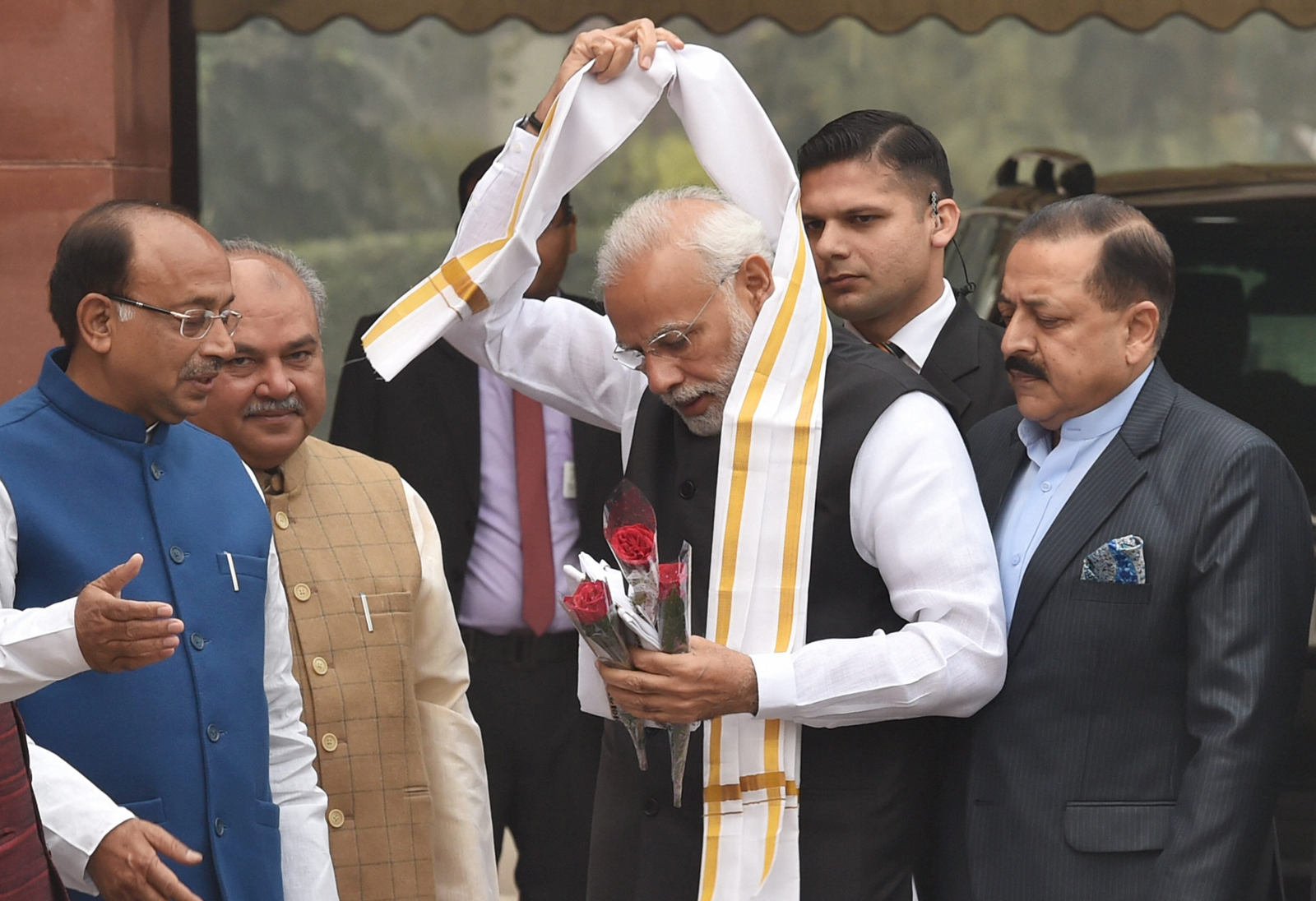 Prime Minister Narendra Modi removes a stole given to him by a minister upon his arrival at the Parliament on the first day of the winter session in New Delhi, December 11, 2018