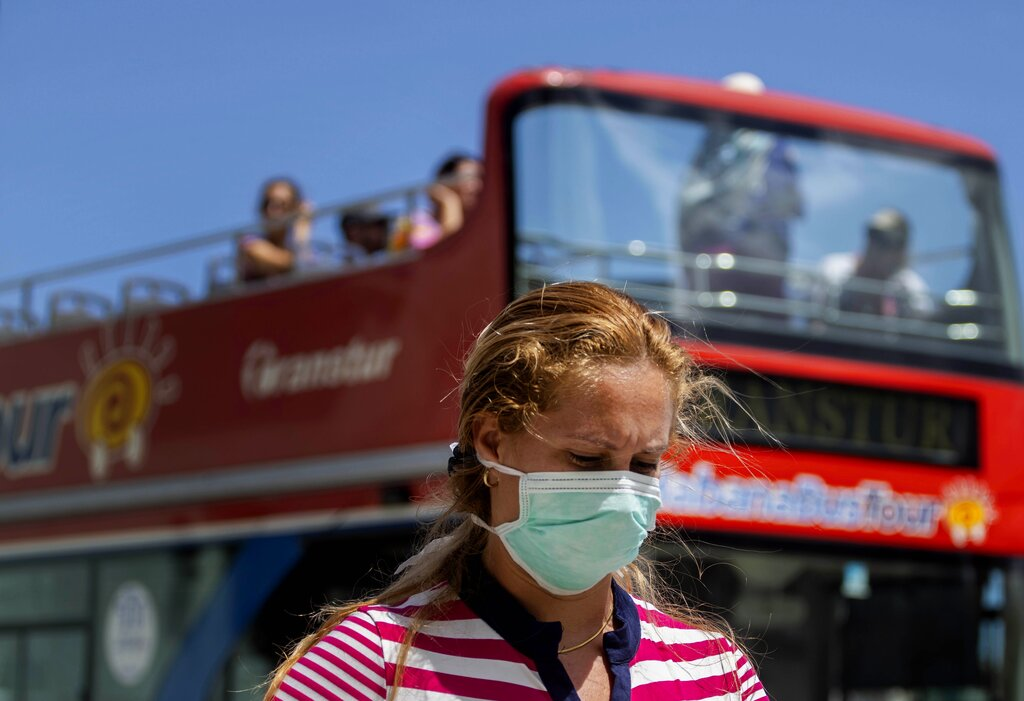 A woman wearing a mask as a precaution against the spread of the new coronavirus walks on the sidewalk as a tourist, double decker bus passes by in Havana, Cuba, Friday, March 20, 2020.
