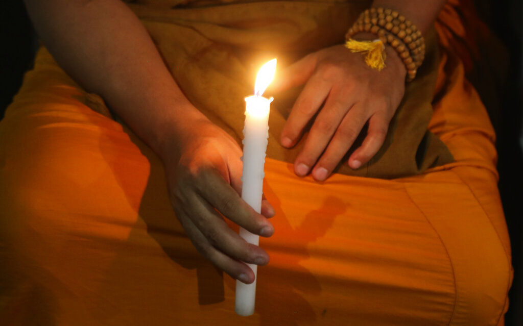 A Buddhist monk holds a candle and prays for a deadly virus outbreak to stop spreading, in Mumbai, on Thursday,