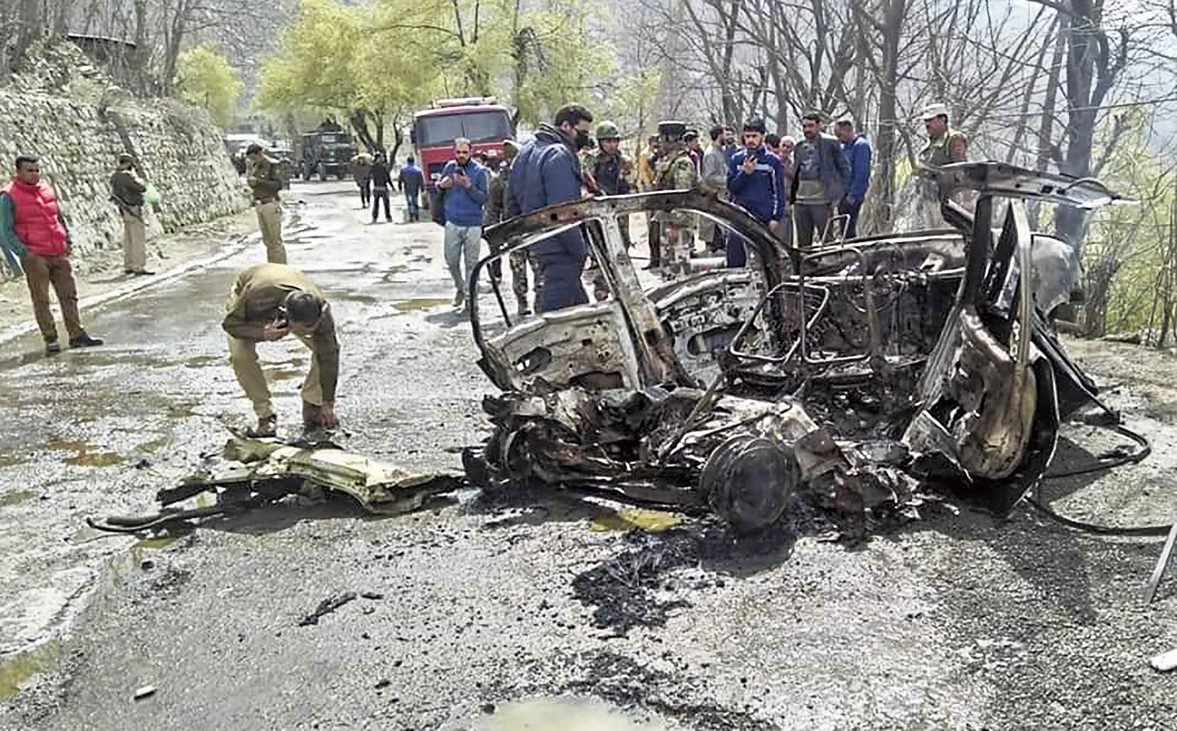 Officers inspect the mangled remains of the car that exploded on the Jammu-Srinagar highway.