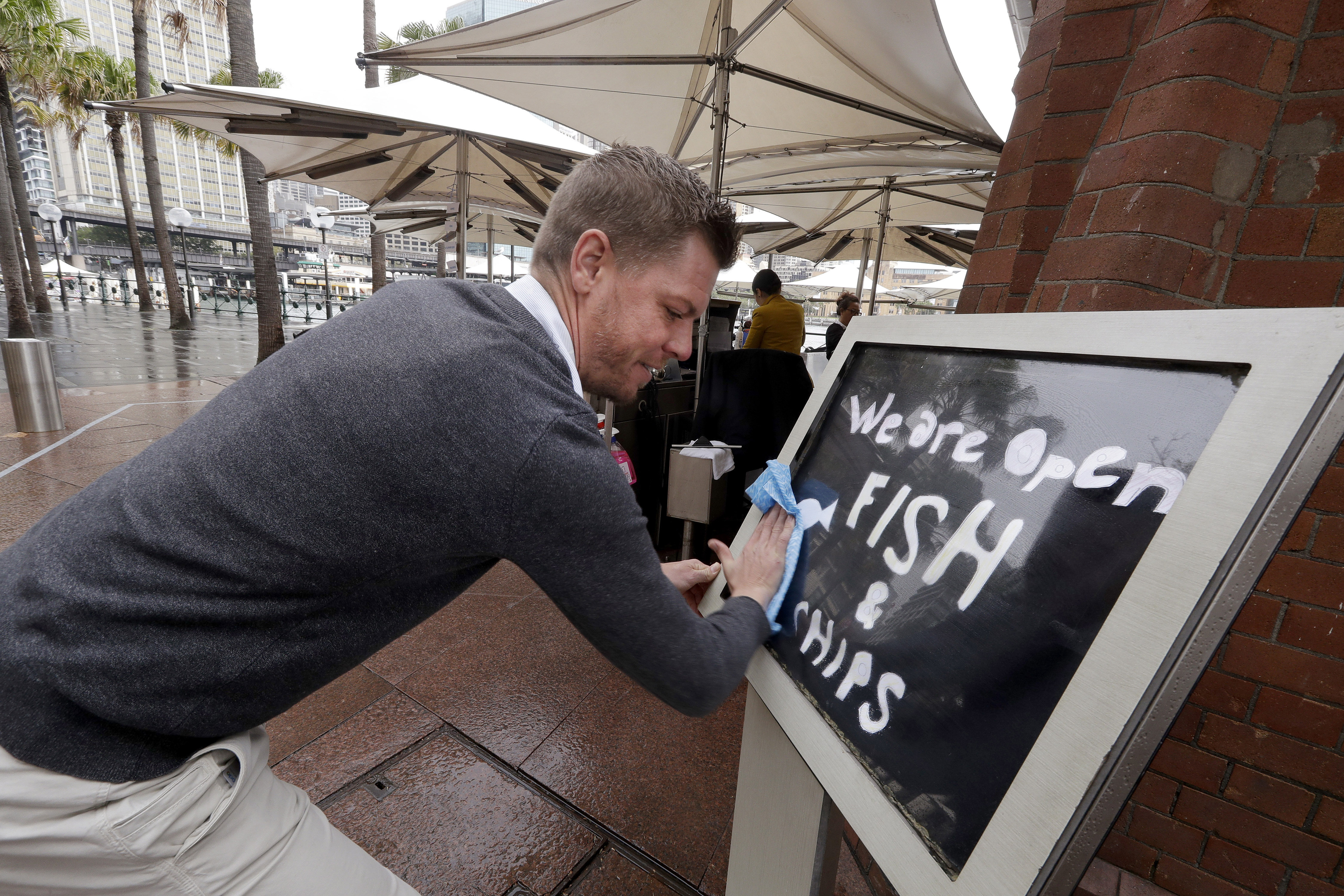 Alec Owes wipes a sign alerting customers that the Sydney Cove Oyster Bar is open as stage 1 of the lifting of Covid-19 restrictions begins in Sydney