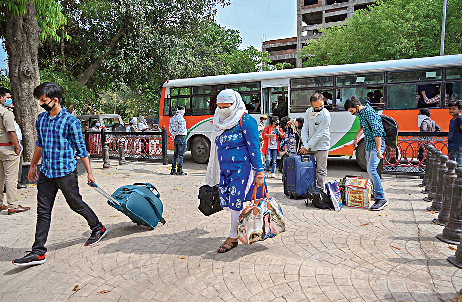 Stranded students from Kota step out a bus arranged by UP government as they arrive at their native place during a nationwide lockdown imposed as a preventive measure against the coronavirus, in Prayagraj, Monday, April 20, 2020.