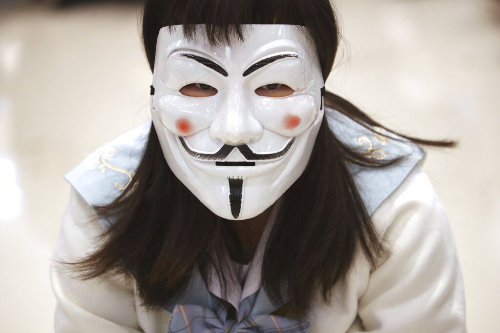 A protester wears a Guy Fawkes mask during a sit-in at a shopping mall to commemorate the four-month anniversary of an assault on commuters and protesters by armed men at a nearby train station in Hong Kong, Thursday, Nov. 21, 2019.