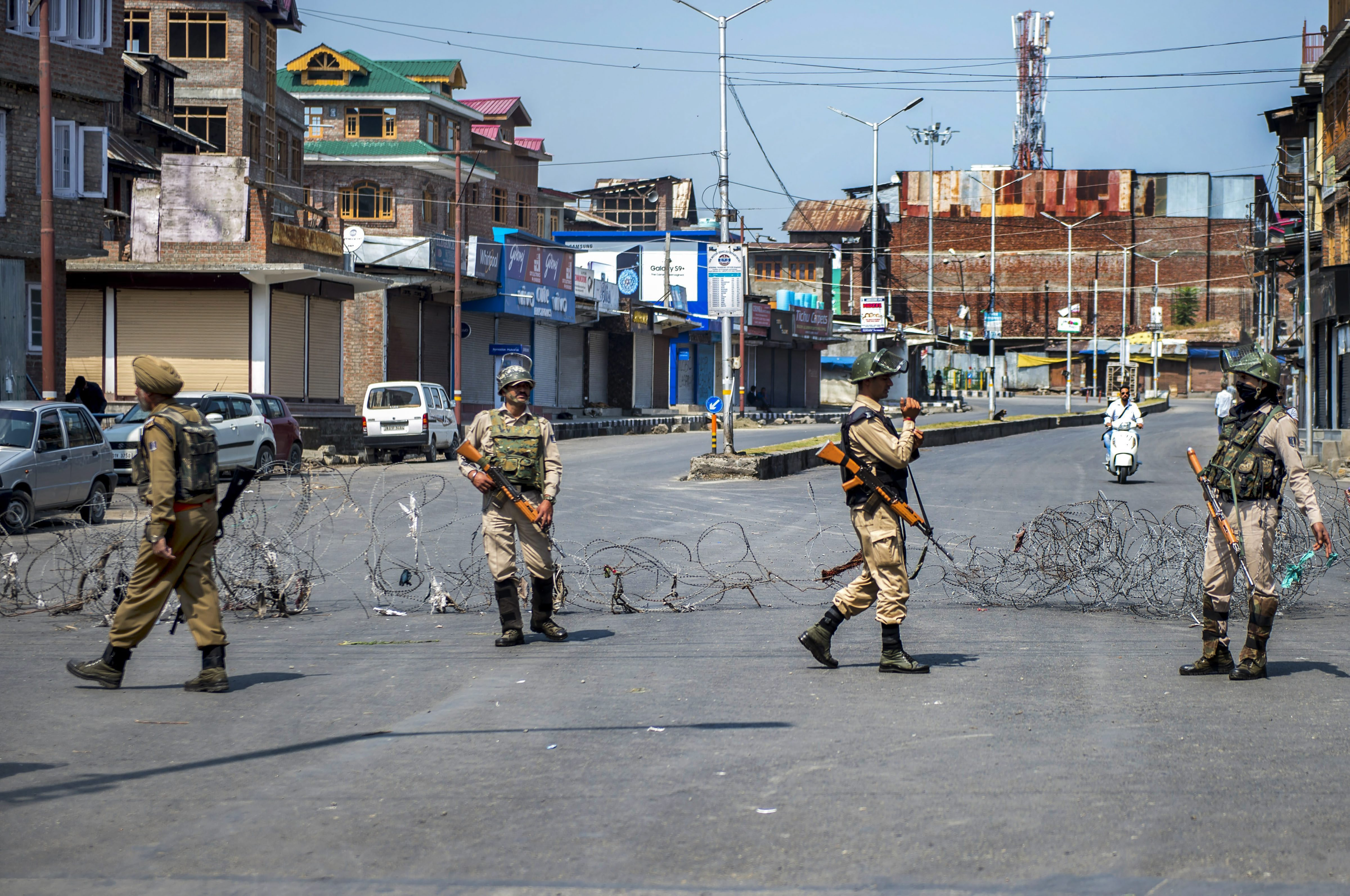 A file photo of security personnel standing guard along a barbed wire in Srinagar, Kashmir.