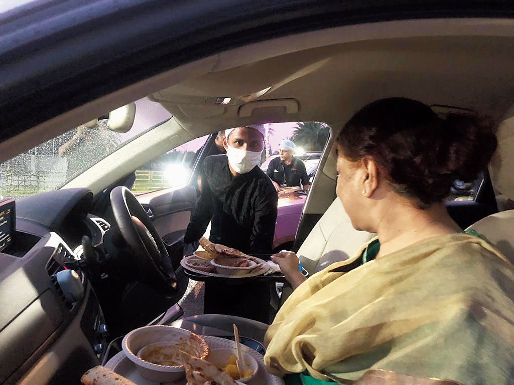 A diner is served in her car parked outside Eco Park's Dhaba Ajante