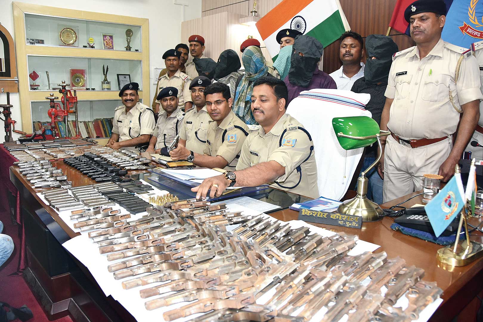 The recovered guns along with the arrested men at Dhanbad SSP's office on Sunday.