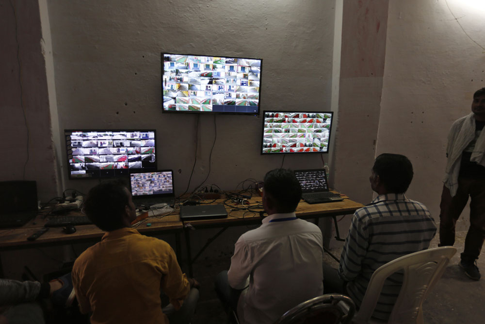 Party workers monitor CCTV camera feed of a vote counting centre in Allahabad on Wednesday, May 22, 2019.