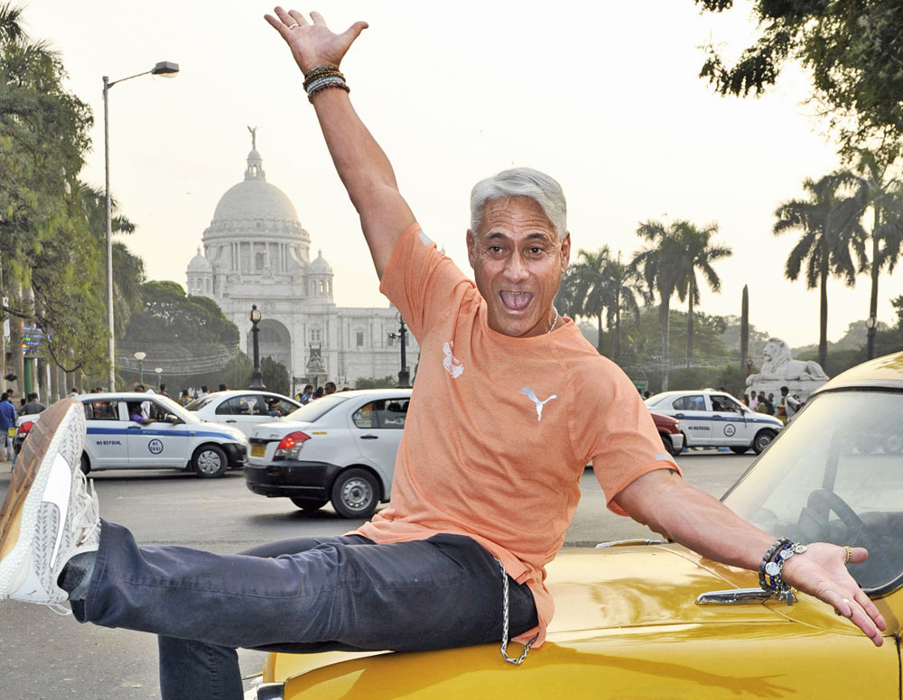 Goofy Greg: Perched on the bonnet of a yellow taxi, Olympian Greg Louganis strikes a pose against the backdrop of the Victoria Memorial on Thursday afternoon. The diving champion is in town as the international event ambassador for the Tata Steel Kolkata 25K, partnered by The Telegraph, on Sunday.