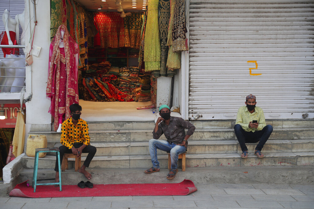 Shopkeepers wearing face mask as a precaution against the coronavirus wait for customer in Hyderabad, Wednesday, May 20, 2020.