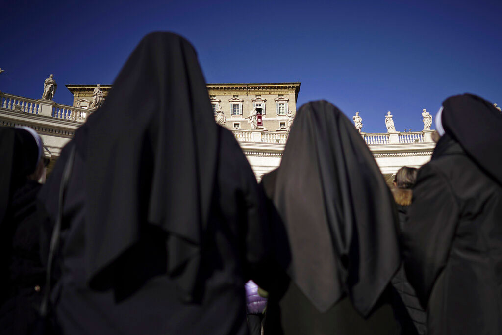 Nuns watch Pope Francis as he delivers his blessings during the Angelus noon prayer at the Vatican on Thursday.