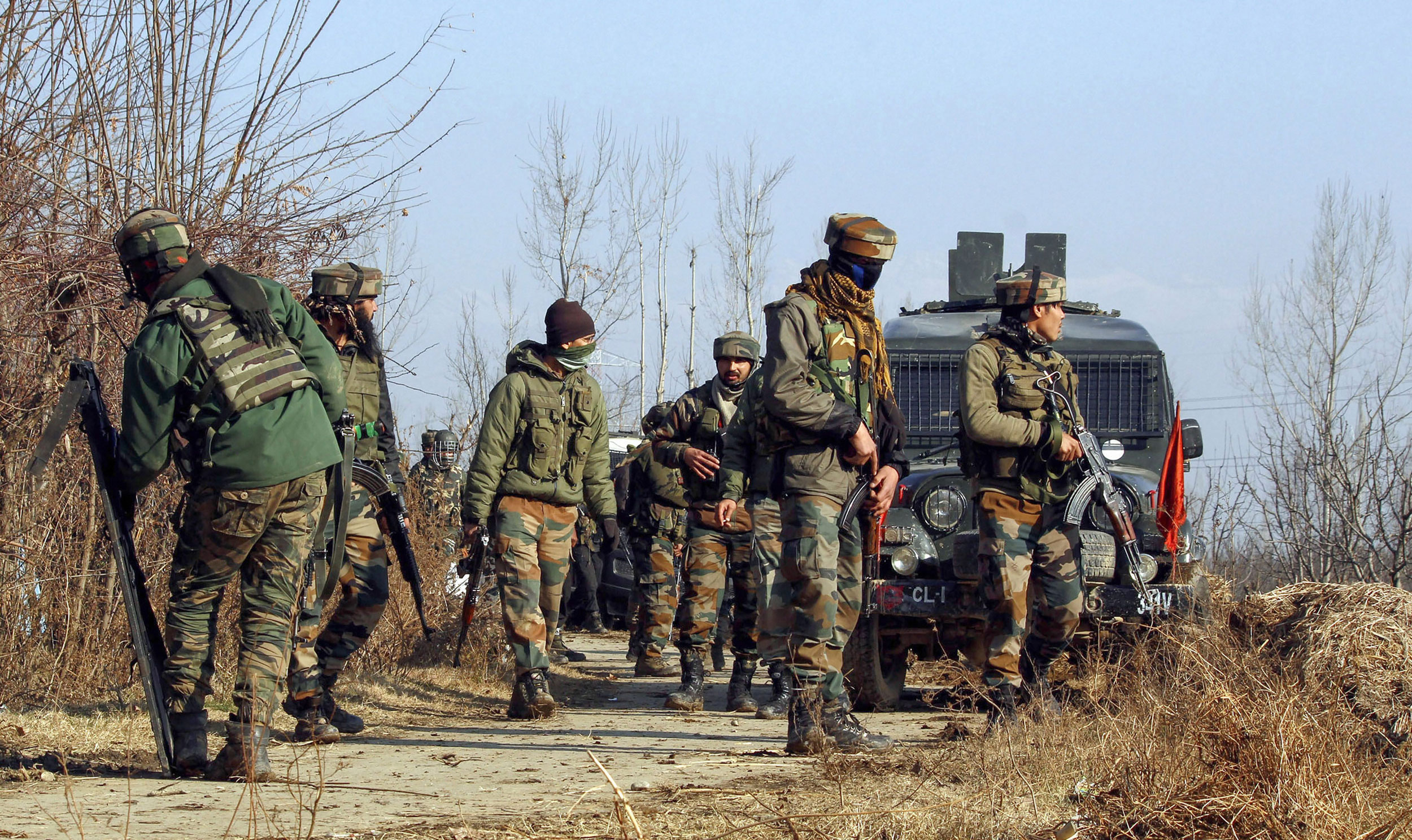 Soldiers take positions during an encounter with the militants at Sirnoo in Pulwama district of south Kashmir, on Saturday.