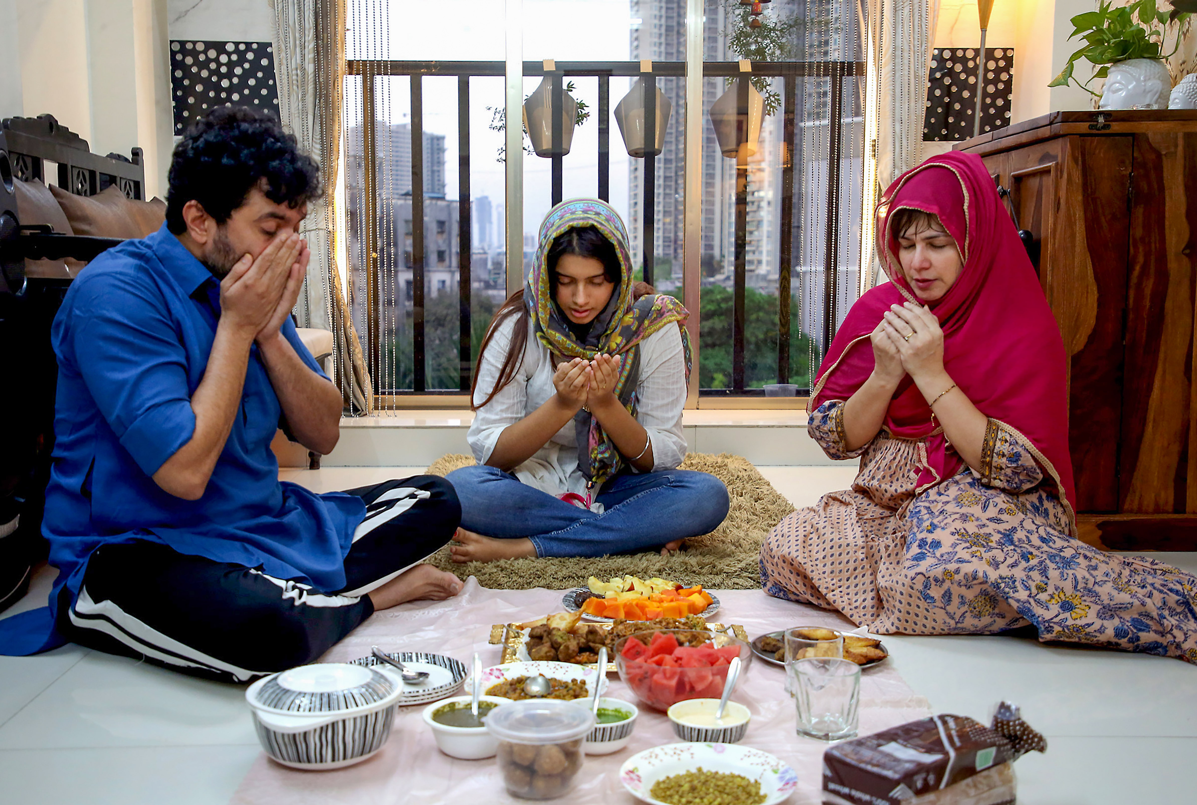 A Muslim family offers prayers before opening their fast with iftar on the first day of holy month of Ramzan during a nationwide lockdown imposed to contain the spread of coronavirus, in Mumbai, Saturday, April 25, 2020